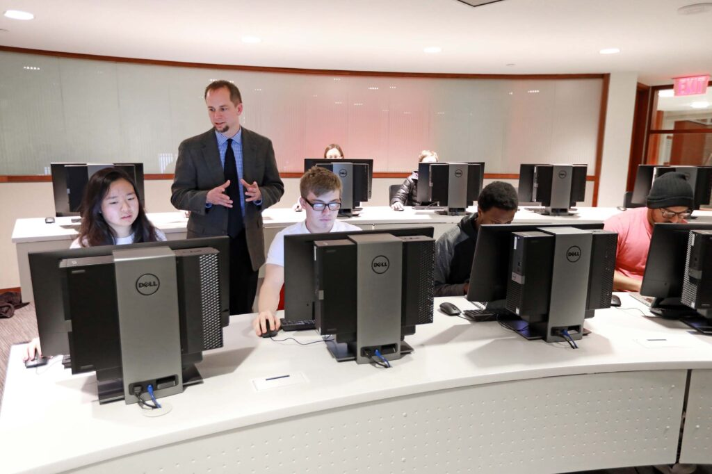 Students using the Instruction Room, a space with ten computer terminals on desks set in an auditorium style.