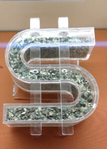 Shredded US dollar money currency displayed in a clear souvenir case shaped in a dollar symbol ($).