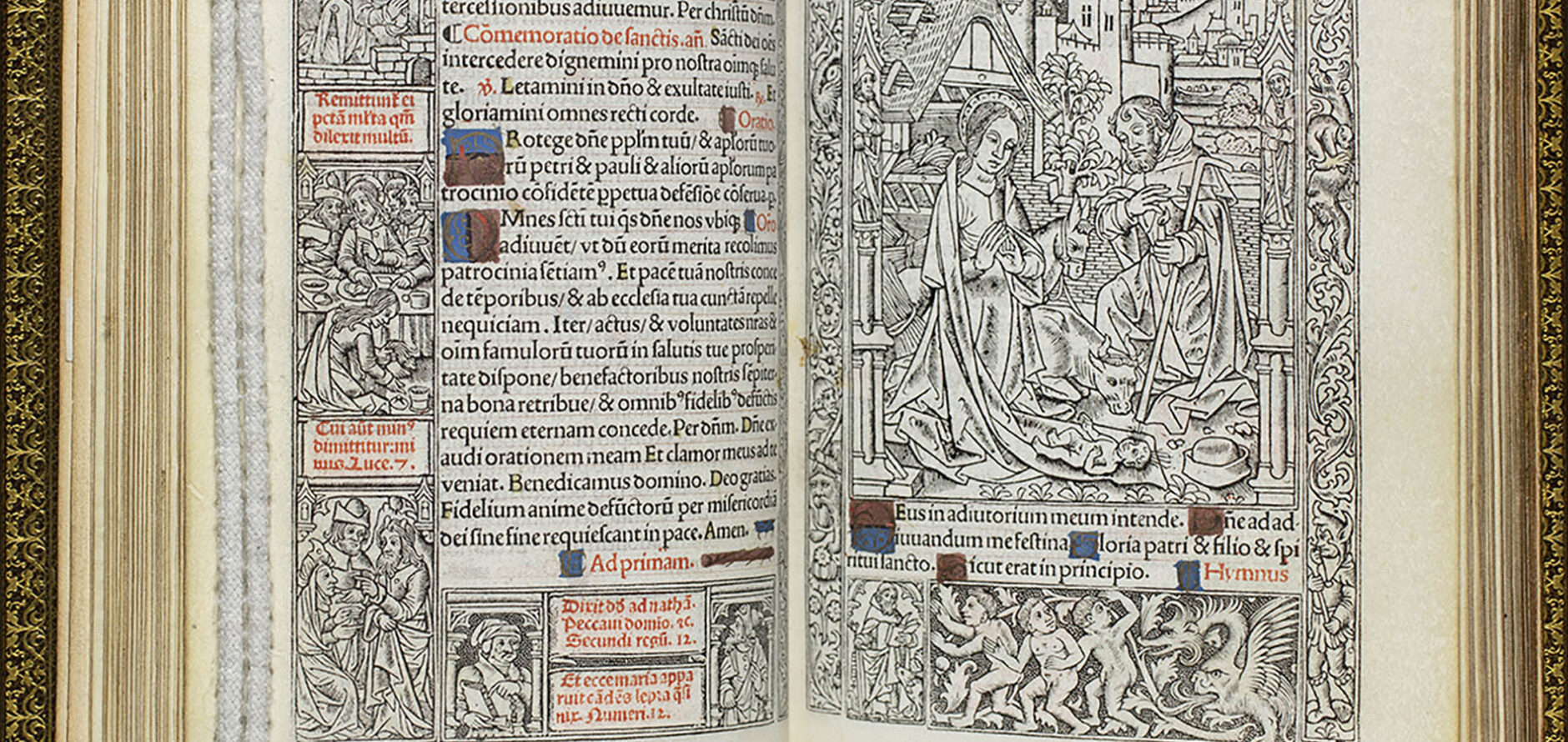 A two-page spread of The Book of Hours. One page has text, some of which is written in red, and the other boasts a black-and-white nativity scene with Joseph and Mary accompanied by a cow kneeling in front of the infant Jesus with an intricately detailed outline of the city skyline behind them.