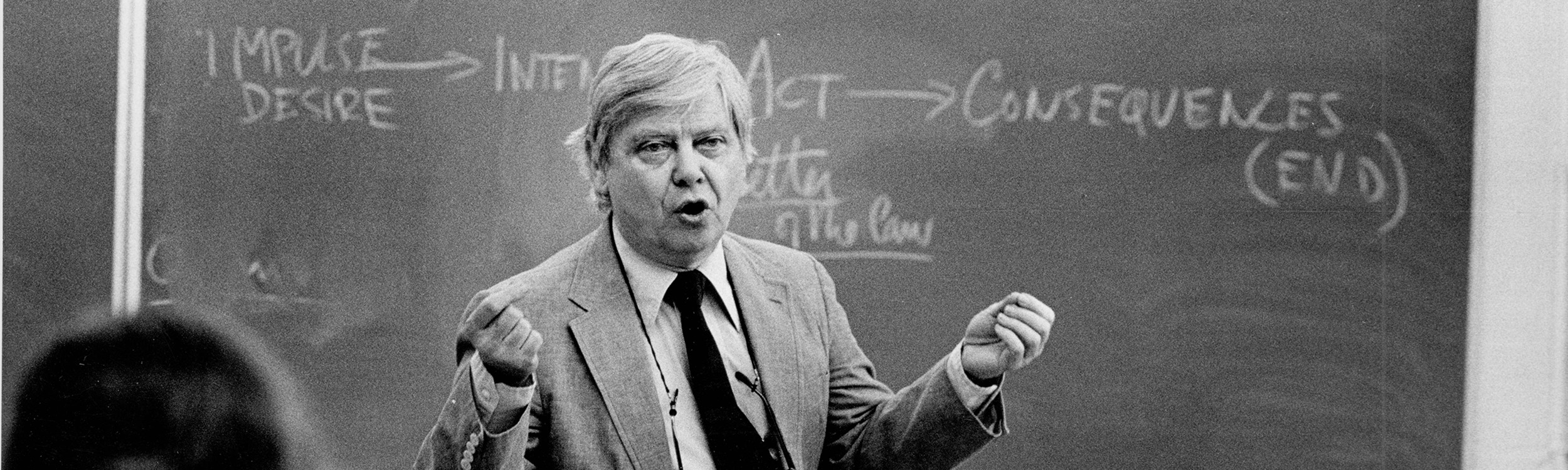 Gass stands in front of a chalkboard in a suit and tie. The photograph has captured him mid-speech during a lecture.