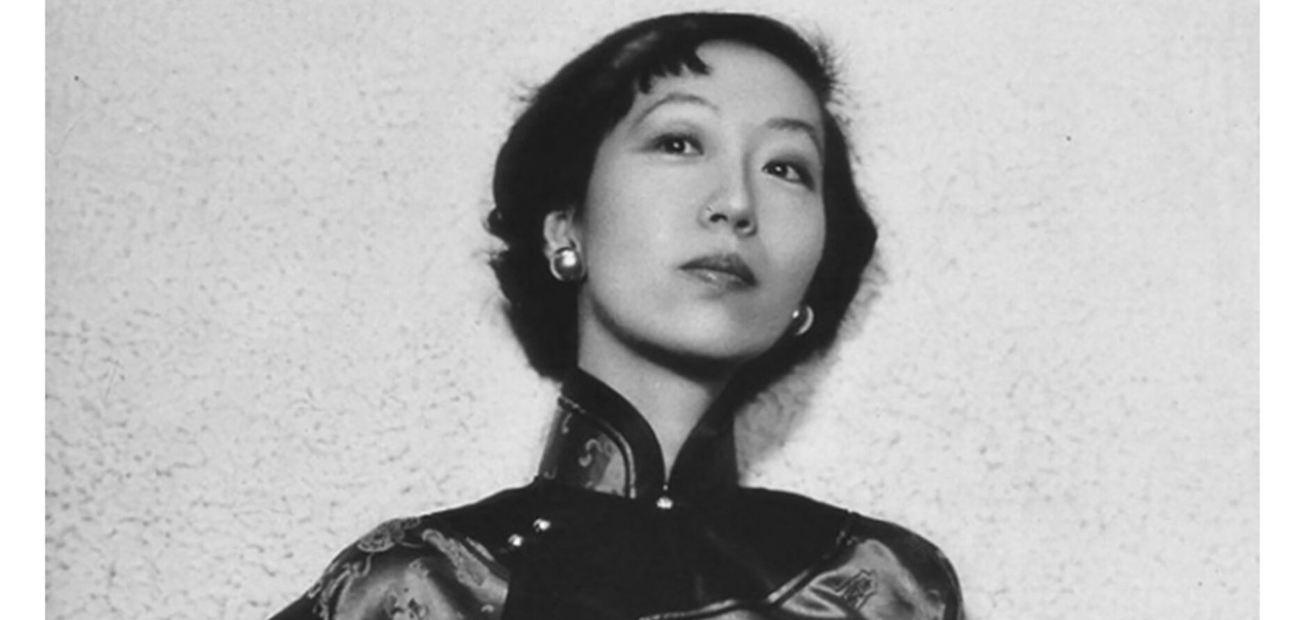 Eileen Chang has short, cropped hair and is wearing oversized earrings with a high neck, three-quarter length sleeved silk top.