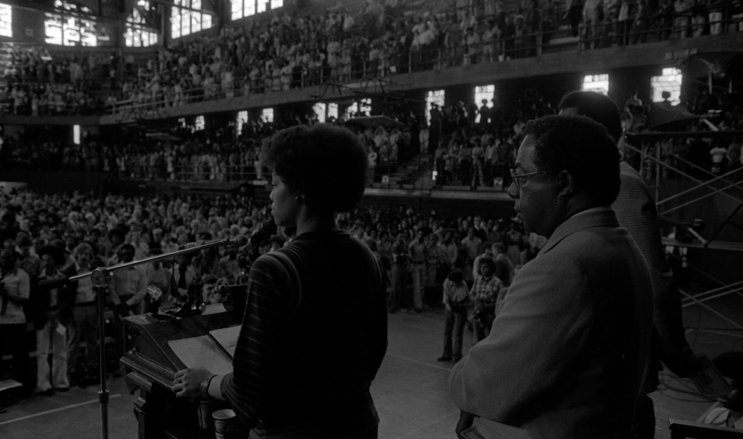 Jan Taylor is speaking at a podium to a large crowd gathered for Assembly Series speaker, Alex Haley.