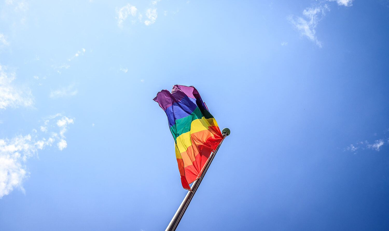 Rainbow pride flag being flown against the background of a crisp blue sky.