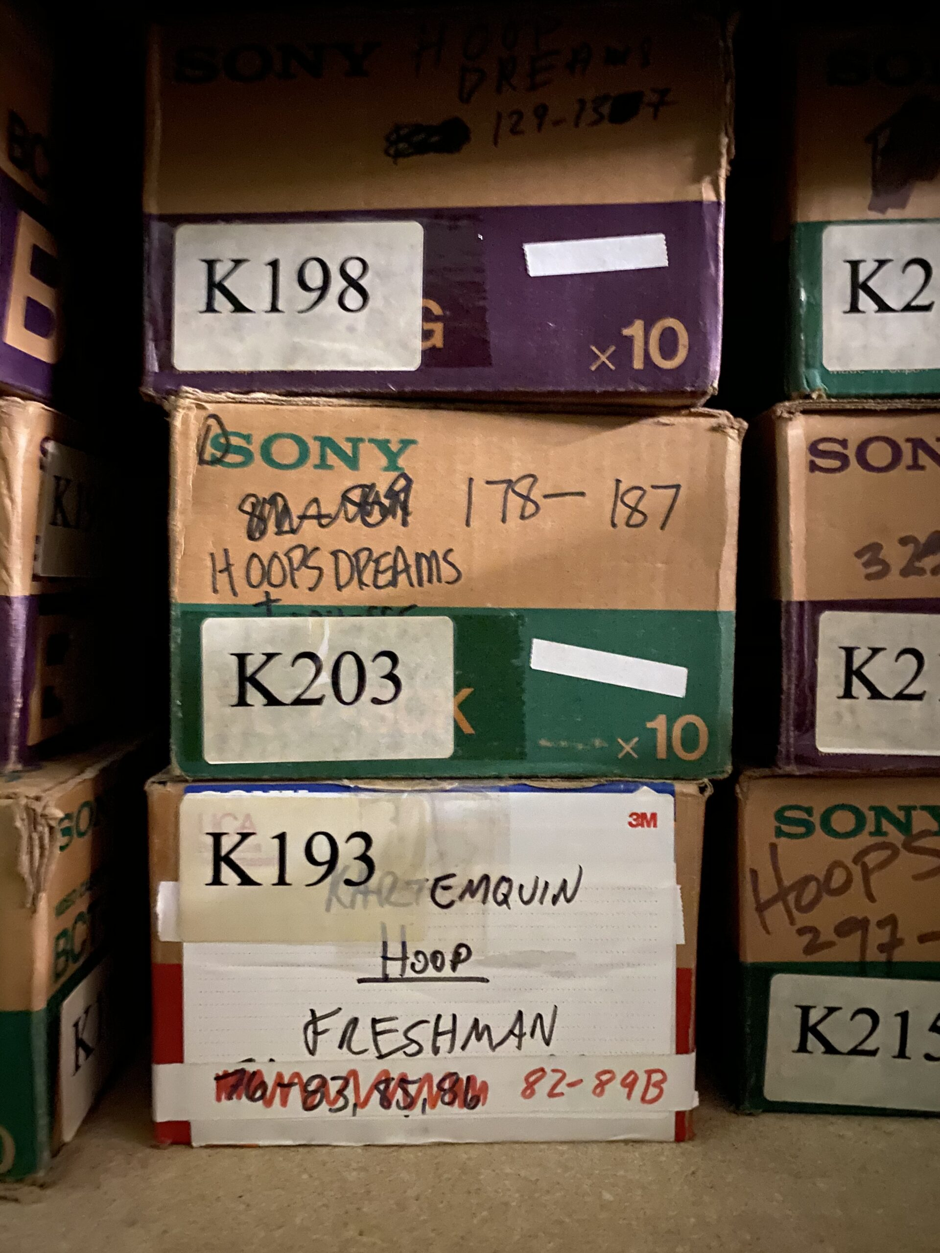"""Small boxes of Sony reel film from the Kartemquin Collection, most with labels reading """"Hoops"""" or """"Hoops Dreams."""""""