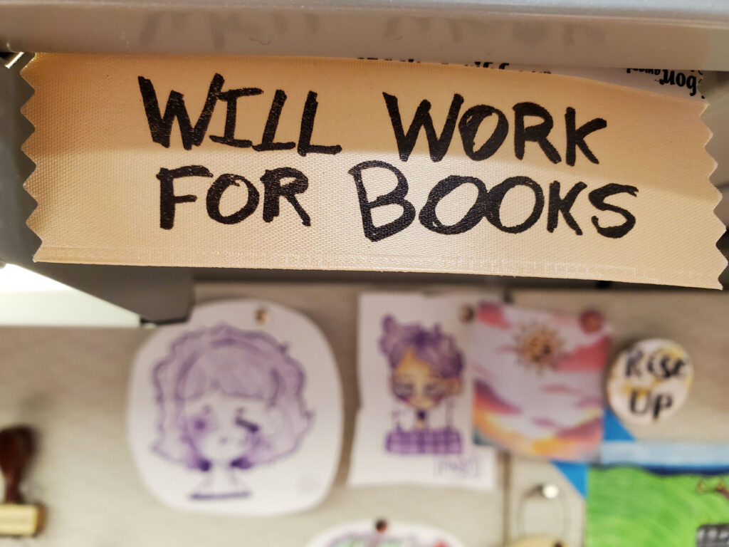 """Handwritten decoration on a staff member's desk that reads """"will work for books"""" in all-caps."""