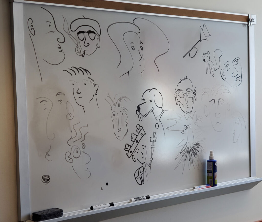 Doodles done on a white board in an office. The doodles are mostly of faces, but a dog and a squirrel make an appearance as well.