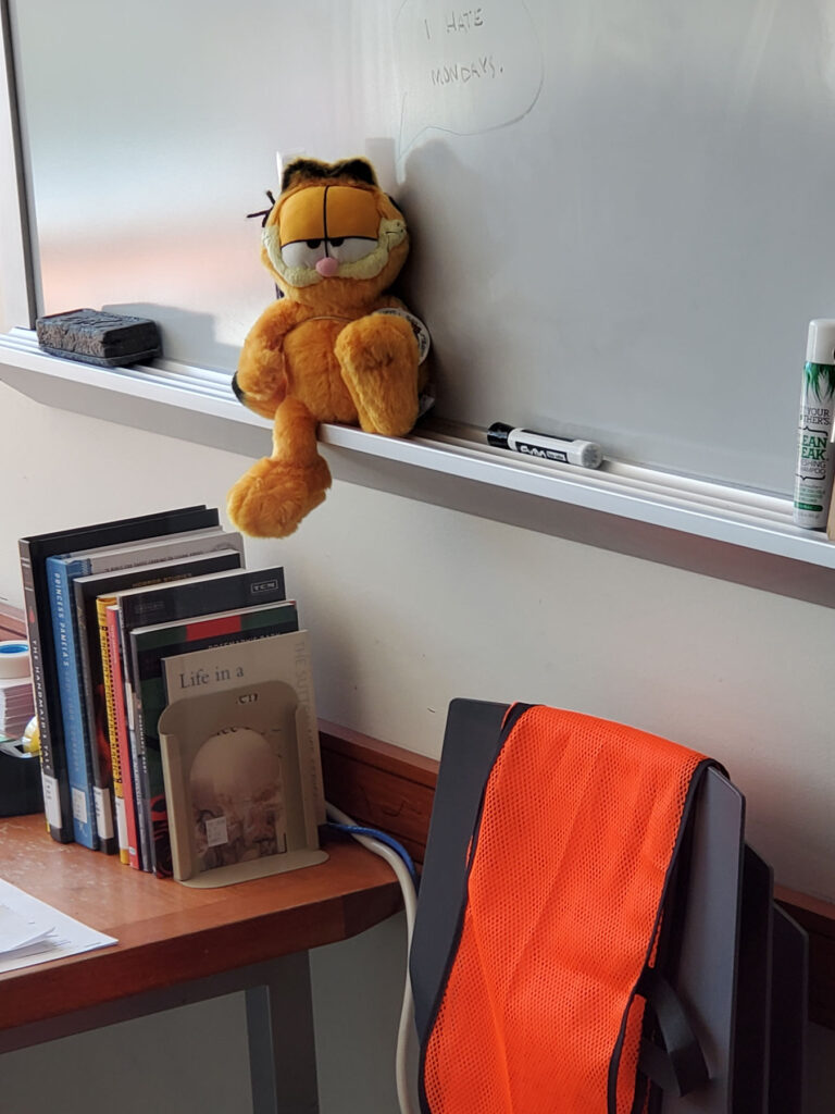 A Garfield the cat stuffed animal lounging on the marker tray of a white board.