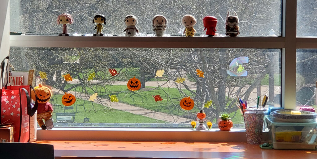 Staff member's desk with Funko Pops and yarn knitted super heros on display. There are Halloween decorations on the window.