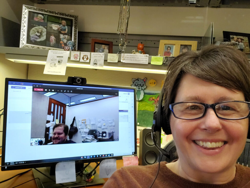 Staff member Ehrstein at their desk with headphones on while a coworker, Brady, is displayed in a Zoom window on their computer during a virtual meeting.