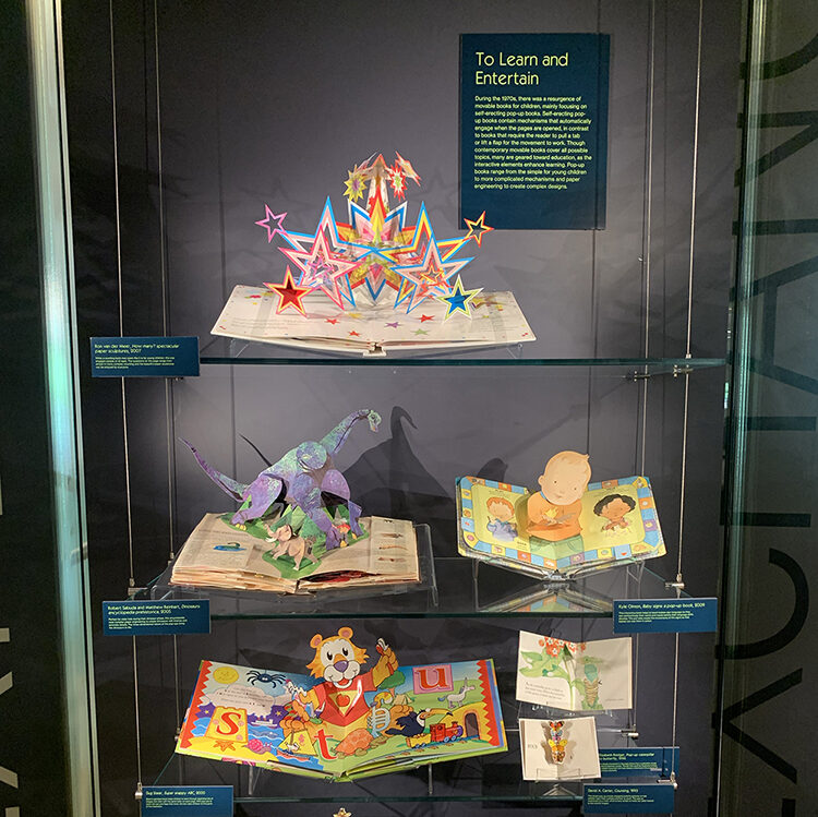 """Display titled """"To Learn and Entertain,"""" part of the Moving Magic exhibition. The display features eight colorful, educational popup books of various sizes."""