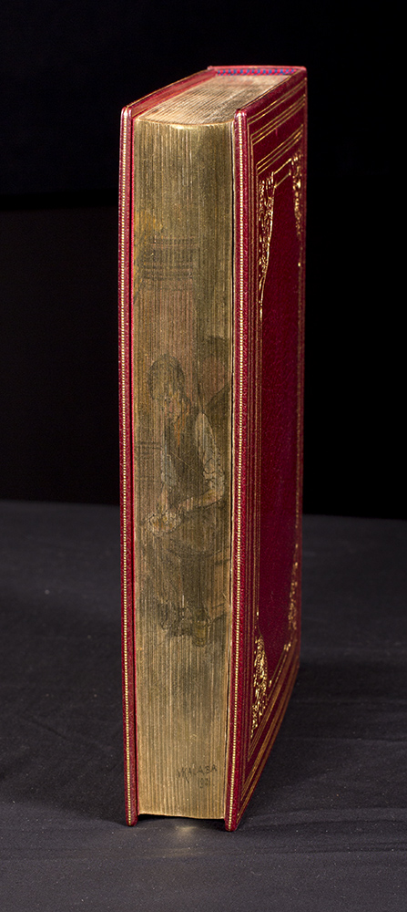The book with the fore edge painting is closed and shows an image of a seated human figure working on crafts.