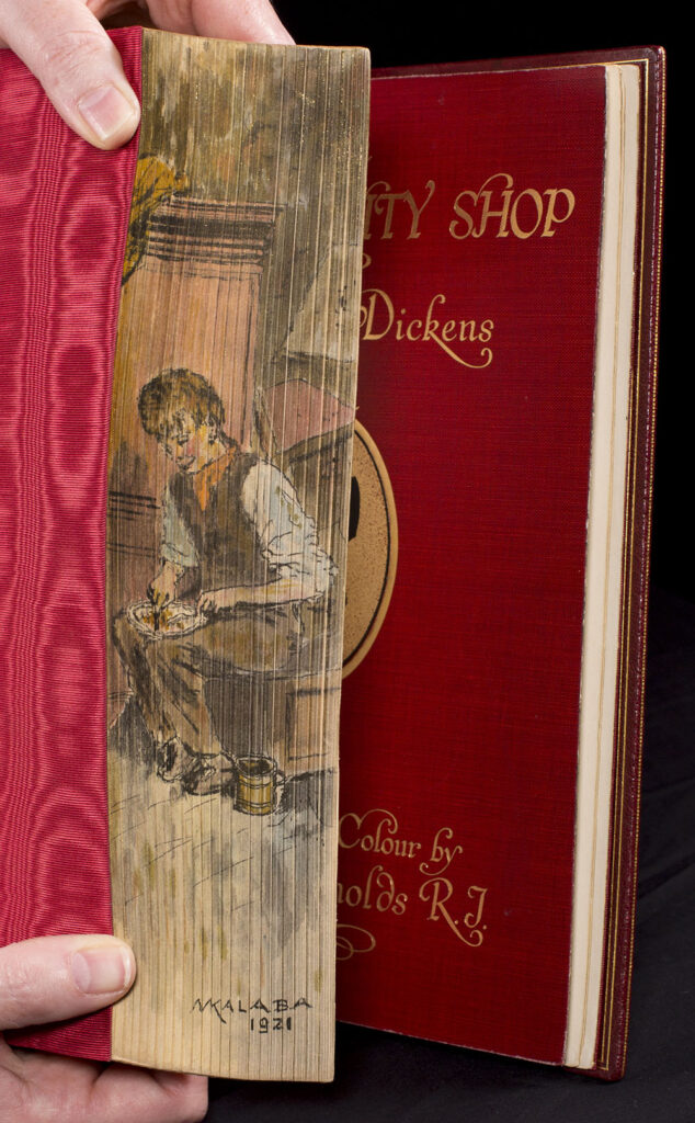 The fore edge painting is manually angled to display and showcases a seated human figure whittling at something in their lap.