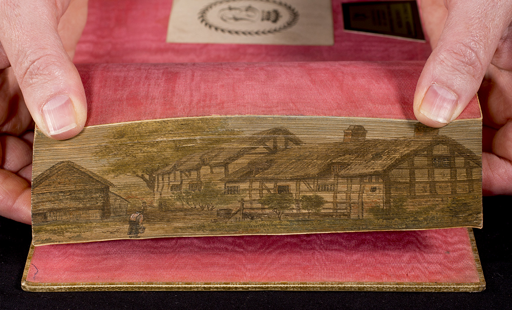 The fore edge painting has a depicting of two Tudor style homes with thatch roofs and a barn.