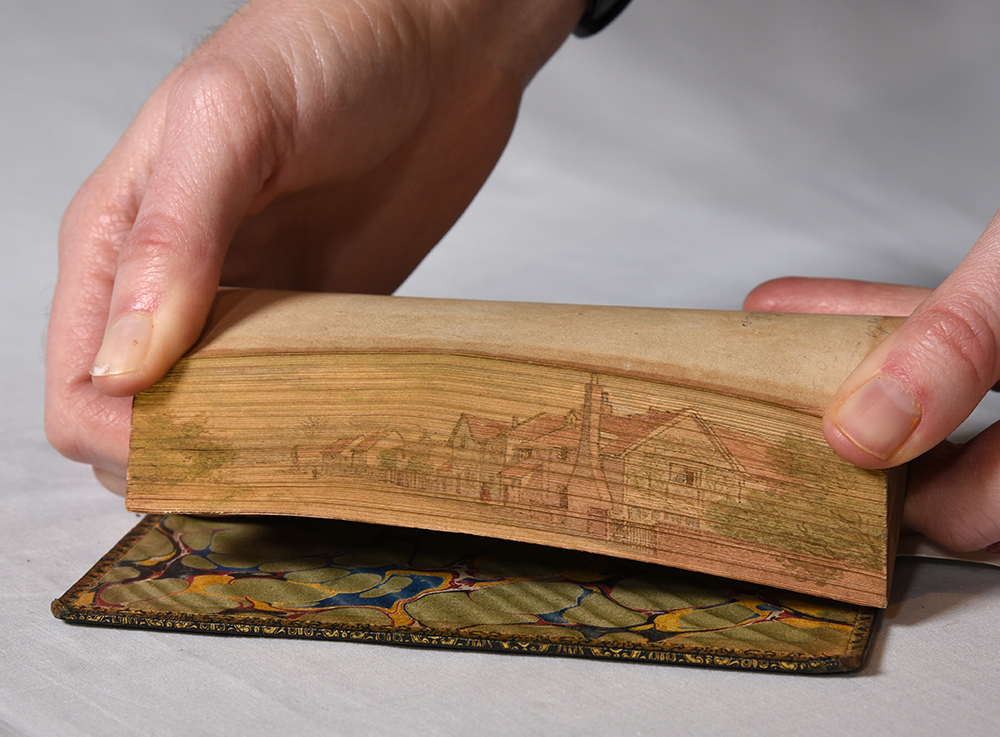 The fore edge is a painting of a village with trees on one side of a lane and row homes on the other. One can also see the stone fence and chimney of the closest house.