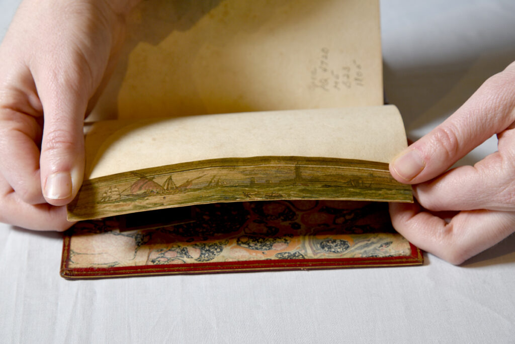 The fore edge painting depicts two ships sailing out to see and a lighthouse on the shore.