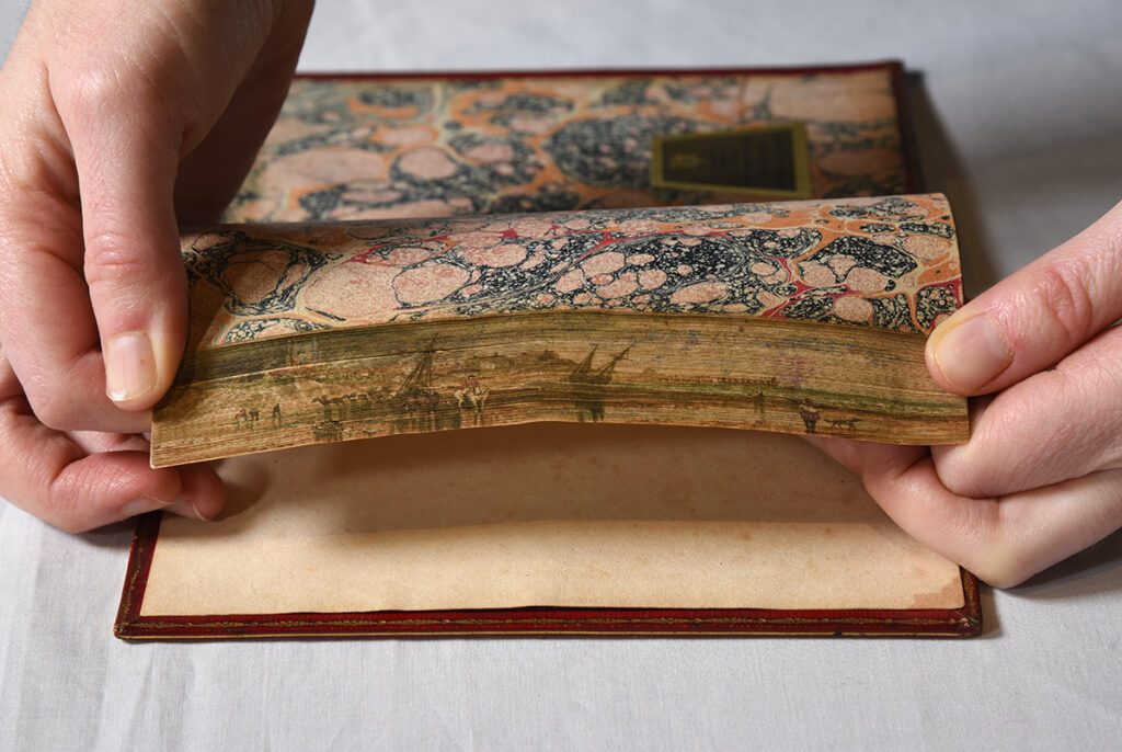The fore edge painting shows the shore of a river with a dock where two ships are tied. A lone man sits astride a horse in the water looking out to sea - look out at the viewer.