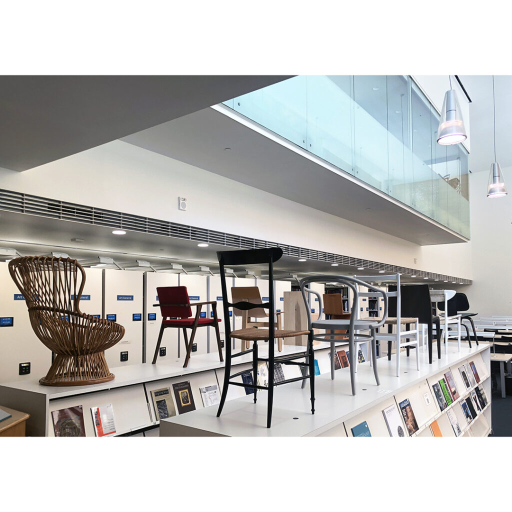The photo is of the exhibition, chairs of various design on top of magazine shelves inside the Art & Architecture Library.