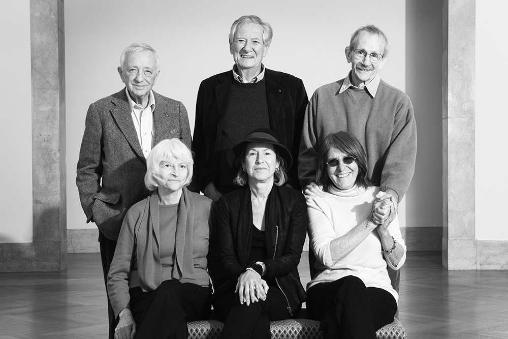 The image shows six of the seven members of the Academy Committee. The image has the three men of the Committee standing behind the three, seated women of the Committee.