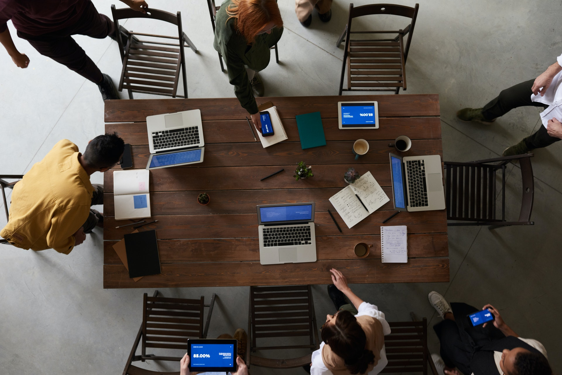 Students gathered around a rectangular table with laptops and notebooks in hand.
