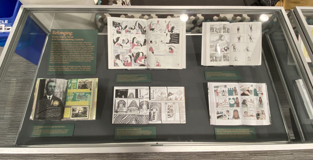 The image shows a display case with five graphic novels open in two-page displays. Each graphic novel has a placard alongside it explaining the individual texts.
